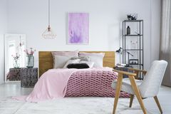 Pastel bedroom with watercolor painting. Elegant, white armchair facing a bed with pink bedclothes and a watercolor painting in pastel bedroom stock photo
