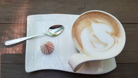 Elegant white cup of cappuccino with tea spoon and small twirl meringue on white stylish plate. White cup of cappuccino with tea spoon and small twirl meringue stock image