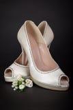 Elegant white female shoes on dark background. Bride shoes Royalty Free Stock Images