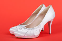 Elegant white female shoes on red Royalty Free Stock Photos