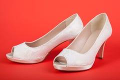 Elegant white female shoes on red background Stock Photo