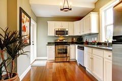 Elegant white and green kitchen with cherry floor. Royalty Free Stock Photos