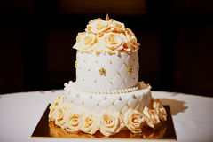 Elegant white wedding cake with roses in 2 tiers. Elegant white wedding cake with cream roses in 2 tiers Stock Image