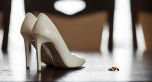 Elegant white wedding shoes and luxury golden wedding rings Royalty Free Stock Image