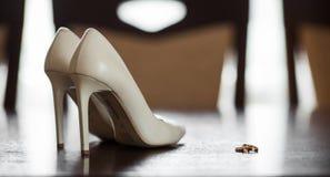 Elegant white wedding shoes and luxury golden wedding rings Royalty Free Stock Image