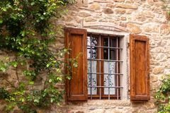 Wooden shuttered window with climbing roses in Tuscany royalty free stock photo