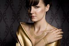 Elegant woman. Portrait of elegant woman wearing golden necklace and bracelet, over wallpaper background Stock Image