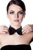 Elegant woman adjusting bow tie Royalty Free Stock Image