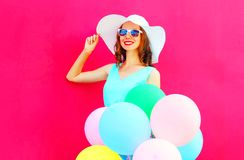 Elegant woman and air colorful balloons is having fun on pink. Elegant woman and air colorful balloons is having fun on a pink background Stock Photo