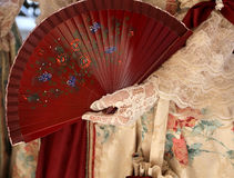 Elegant woman with an ancient ceremonial dress and the fan in he. R hand with glove Royalty Free Stock Photography