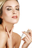 Elegant woman applying perfume on her body Stock Images