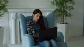 Elegant woman in armchair chatting online via laptop stock video footage