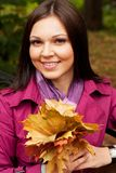 Elegant woman with autumn leaves sitting on bench Stock Photos