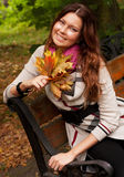Elegant woman with autumn leaves sitting on bench Stock Images