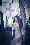 Elegant woman with balloons in wood Royalty Free Stock Images