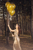 Elegant woman with balloons in wood Royalty Free Stock Photography