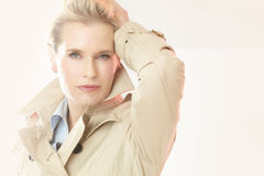 Elegant Woman. Beautiful modern elegant woman indoors wearing trench coat in studio Stock Image