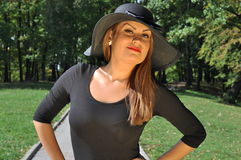 Elegant woman in a black dress and elegant hat Royalty Free Stock Photography