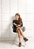 Elegant woman in black dress posing in white chair at studio Stock Photo