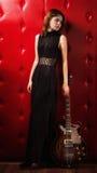 Elegant woman in black with guitar. Elegant woman in black with electric guitar Stock Photography