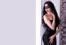Elegant woman in black mask. Sexy young woman in black dress. Retro glamor woman. Royalty Free Stock Photography