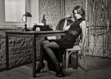 Elegant woman in black with the old typewriter Royalty Free Stock Photography