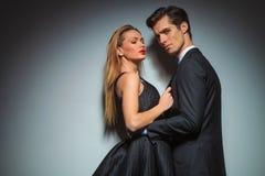 Elegant woman in black pulling man's jacket Royalty Free Stock Photo