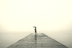 Elegant woman with black umbrella looking infinity in a surreal place Stock Image