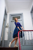 Elegant woman in blue dress poses on the stairs Royalty Free Stock Images