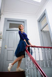 Elegant woman in blue dress poses on the stairs Royalty Free Stock Photography