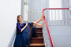 Elegant woman in blue dress poses on the stairs Stock Photo