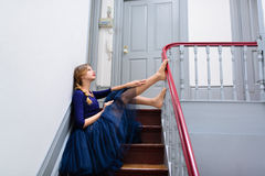 Elegant woman in blue dress poses on the stairs Royalty Free Stock Photos