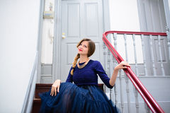 Elegant woman in blue dress poses on the stairs Royalty Free Stock Photo