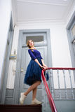 Elegant woman in blue dress poses on the stairs Stock Photos