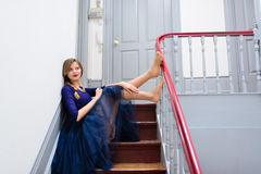 Elegant woman in blue dress poses on the stairs Stock Images