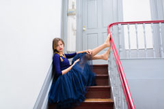 Elegant woman in blue dress poses on the stairs Stock Image