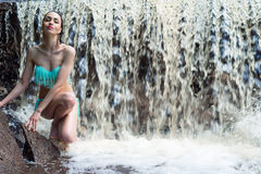 Elegant woman in a blue a swimsuit on background waterfall Stock Photography
