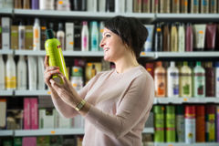 Elegant woman buying hair care products. Elegant female buying hair care products in beauty salon and smiling royalty free stock photo