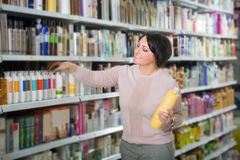 Elegant woman buying hair care products. Elegant female customer buying hair care products in beauty salon and smiling stock images
