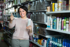 Elegant woman buying hair care products. Elegant female customer buying hair care products in beauty shop and smiling stock photo