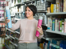 Elegant woman buying hair care products. Positive female customer buying hair care products in beauty salon and smiling stock photos