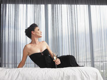 Elegant Woman With Champagne Glass Sitting In Bed Royalty Free Stock Photos