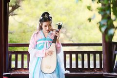 Elegant woman in Chinese traditional drama ancient costume play Chinese lute pipa guitar. Graceful and beautiful chinese girl in hanfu dress, play pipa chinese Royalty Free Stock Image