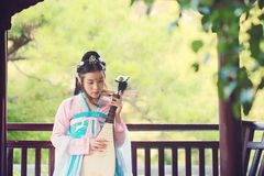 Elegant woman in Chinese traditional drama ancient costume play Chinese lute pipa guitar. Graceful and beautiful chinese girl in hanfu dress, play pipa chinese Stock Image