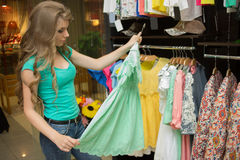 Elegant woman choosing dress in retail store Stock Photography