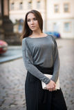 Elegant woman in the city holding white clutch Stock Photography