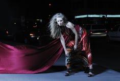 Elegant woman on city street at night Stock Images