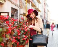 Elegant woman in coat and purple hat on street tourist town with Royalty Free Stock Photo