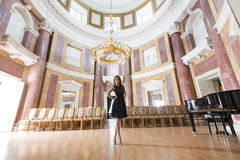 Elegant woman in concert hall. Pretty brunette girl with evening dress and heels posing with happy expression in elegant concert hall near ancient empty seat and Stock Photography