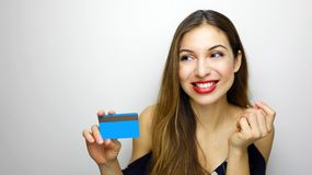 Elegant woman with credit card thinking what to buy looking to the side copyspace on white background.  stock photos